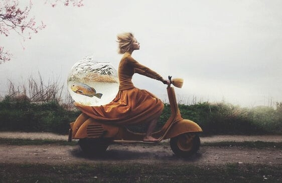 A woman on a motorbike with a fishbowl.