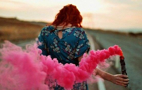 Woman with trail of pink smoke