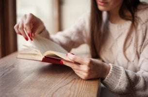 A woman with red nails is reading a book about heartbreak