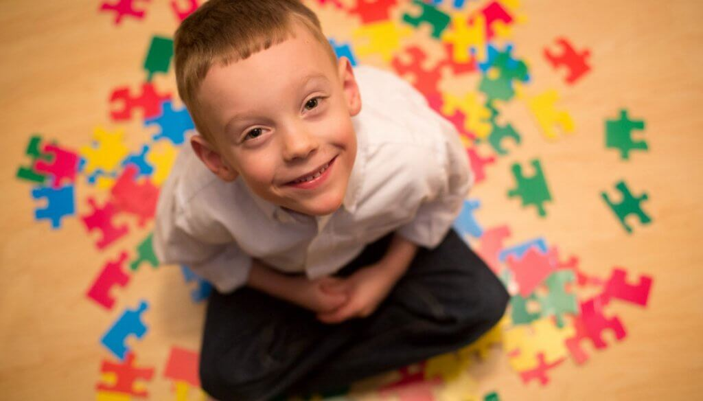 A child with autism and puzzle pieces.