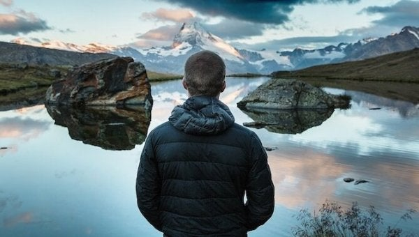 A man looking out at a mountain lake, reflecting and contemplating.