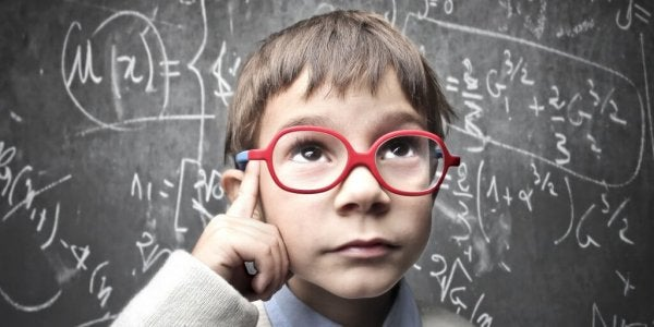 A young student wearing glasses thinking at a chalkboard full of math equations.