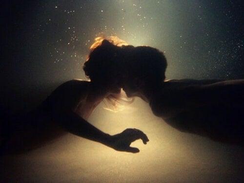 Two people kissing underwater.