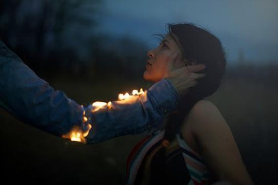 En mann med en brennende arm rekker ut etter en kvinnes ansikt