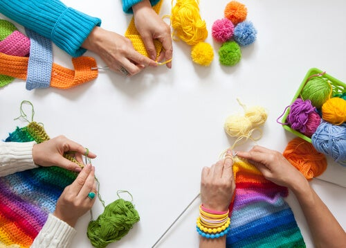 A group of friends knitting colorful crafts together.