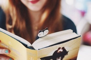 A girl is reading a book with a cat bookmark in it.