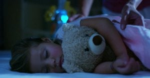 A little girl sleeping with her teddy bear.