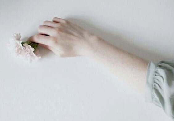 A pale arm holding flowers.