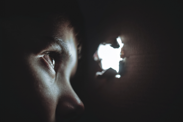A child looking out of a hole in a dark box.
