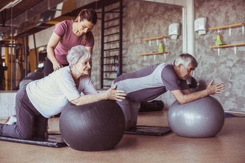 Older people exercising on yoga balls with a trainer.
