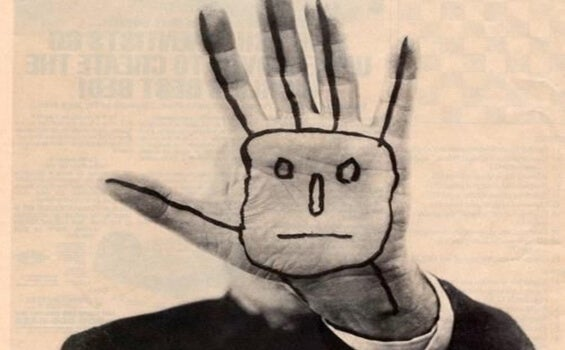 A hand saying stop with a face drawn onto it.