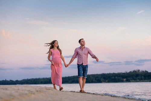 Pregnant woman and her husband walking along the beach.