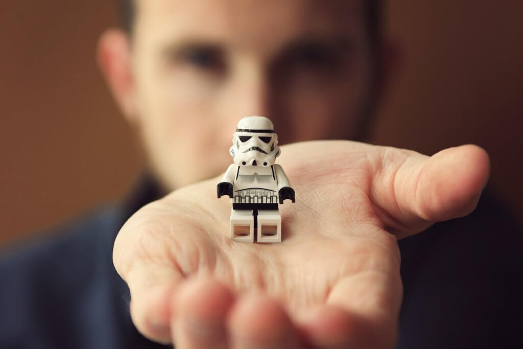 Holding a robot toy LEGO in a hand.