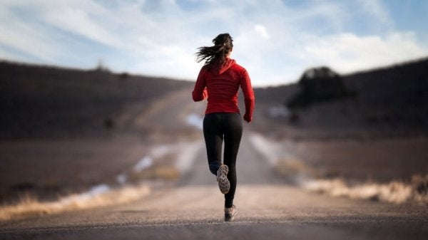 A woman running outside on the road in the country.
