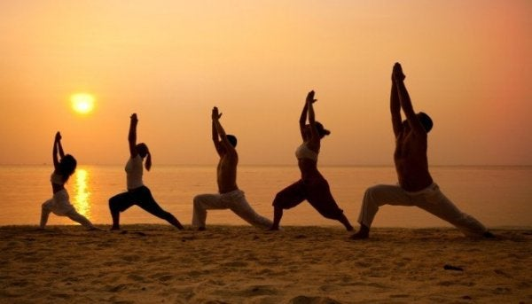 People practicing tai chi on the beach.