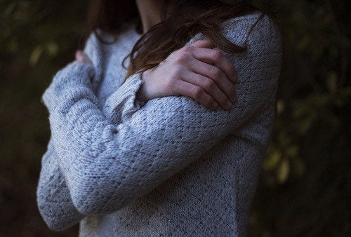 Woman in a sweater hugging self.