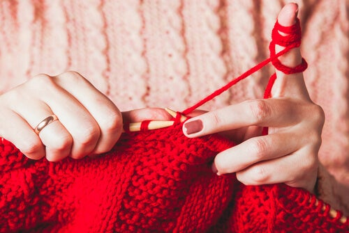A woman knitting with red yarn.
