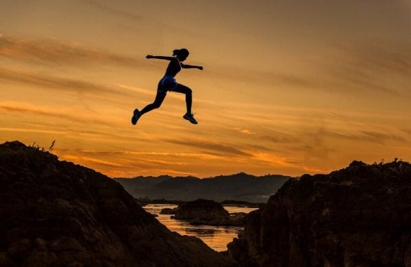 A woman becoming stronger emotionally, leaping over the mountains.