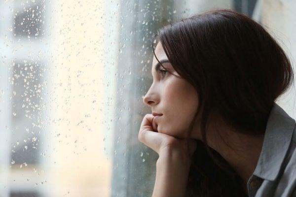 A sad woman gazing out a rainy window.