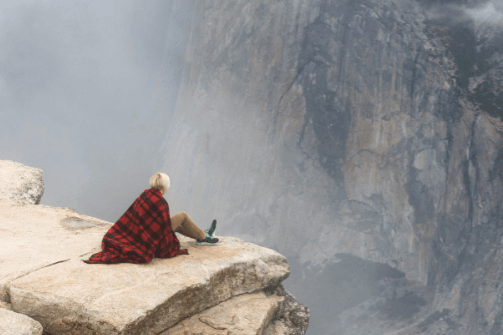 A woman is sitting at the edge of a cliff.