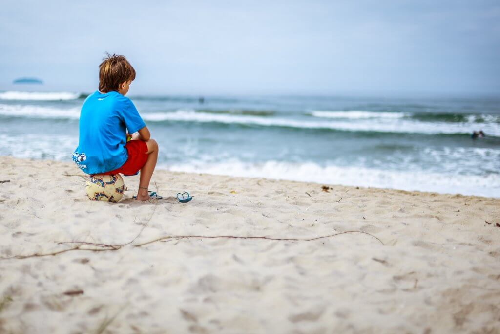 A boy is looking at the ocean while sitting on a soccer ball.
