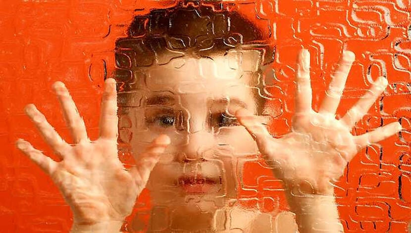 A boy is pressing his palms against a distorted glass.