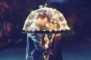 A couple inside a lit up umbrella.