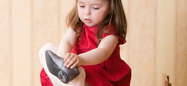 A little girl is putting on her shoe.