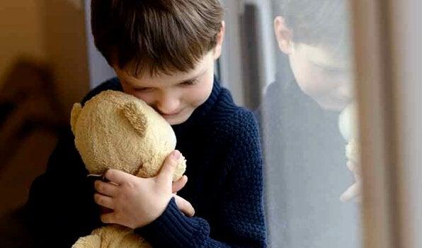 Boy is hugging a teddy bear.