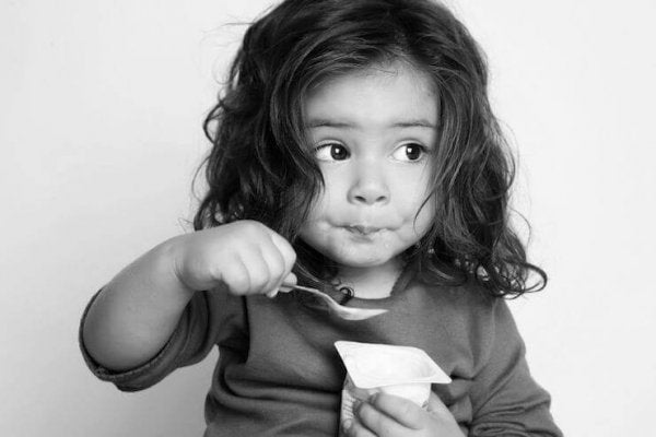 Girl eating yogurt to improve concentration in children.