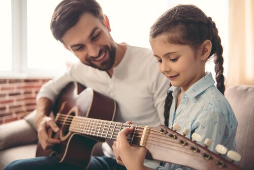 Father and daughter playing the guitar.