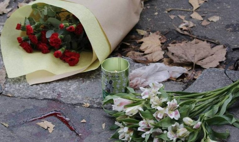 Flowers and a candle on the street after terrorism.