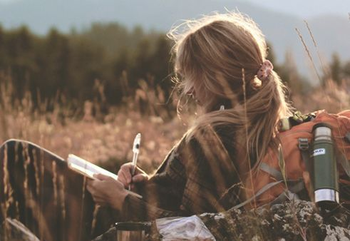 A girl journaling in nature.