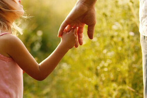 A girl is holding her fathers hand.