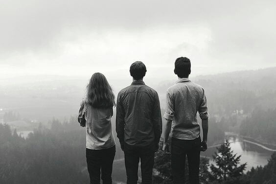 Three friends looking with collective nostalgia at the foggy valley.