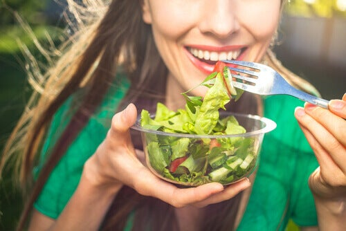 Happy woman eating a salad.