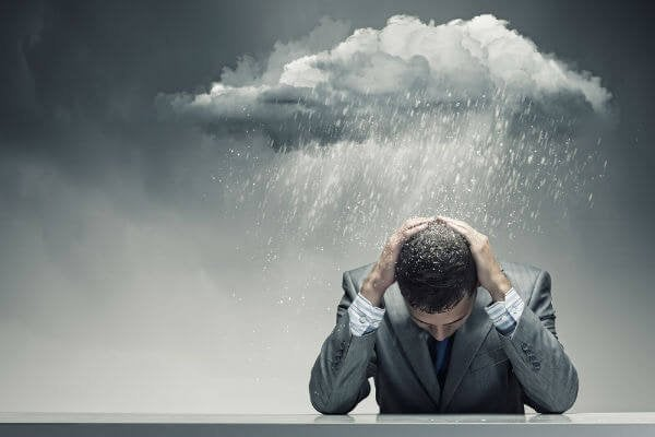 A storm cloud raining over a man in a suit.