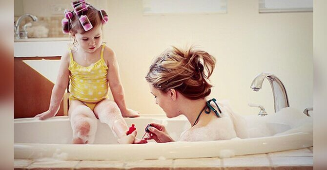 A mother painting her daughter's nails in the bath.