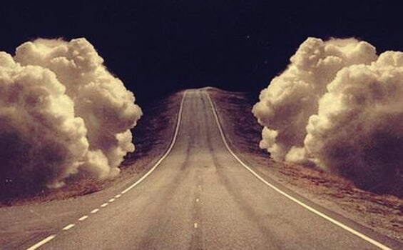 A road with clouds on the sides.
