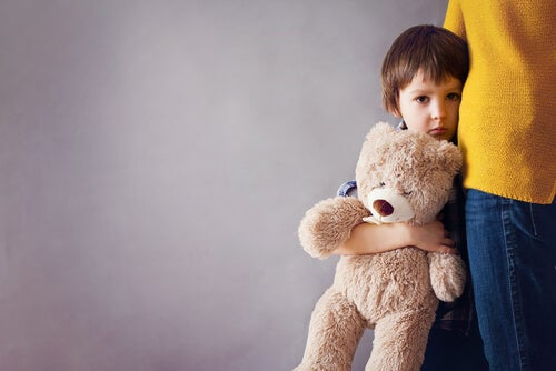 A sad boy clinging to his teddy bear and his mother.