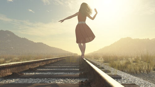 A woman is balancing on railroad tracks.