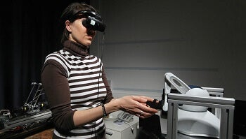 Woman manipulating a robot.