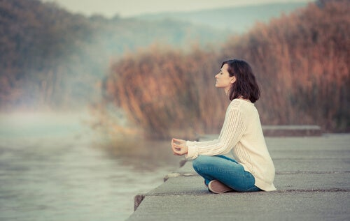 Woman meditating by a lake.
