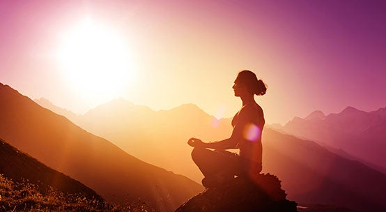 Woman is meditating on a mountain.