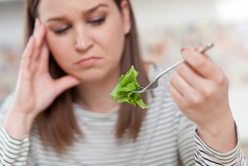 Orthoexia: a woman looking unhappily at lettuce.