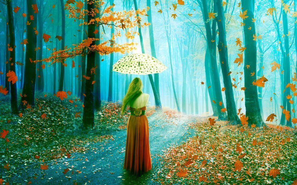 A woman with an umbrella is walking through the woods.