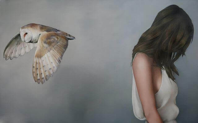 Woman with her head down and a bird flying away from her.