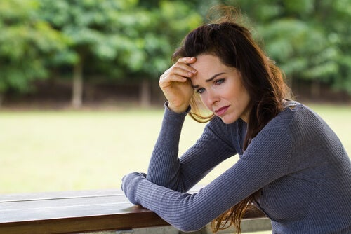 A woman is crying and worried with a hand on her forehead.