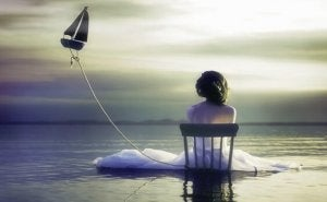 A girl sitting in a chair in the ocean with a flying boat.