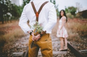 A man is hiding a bouquet of flowers from a girl.